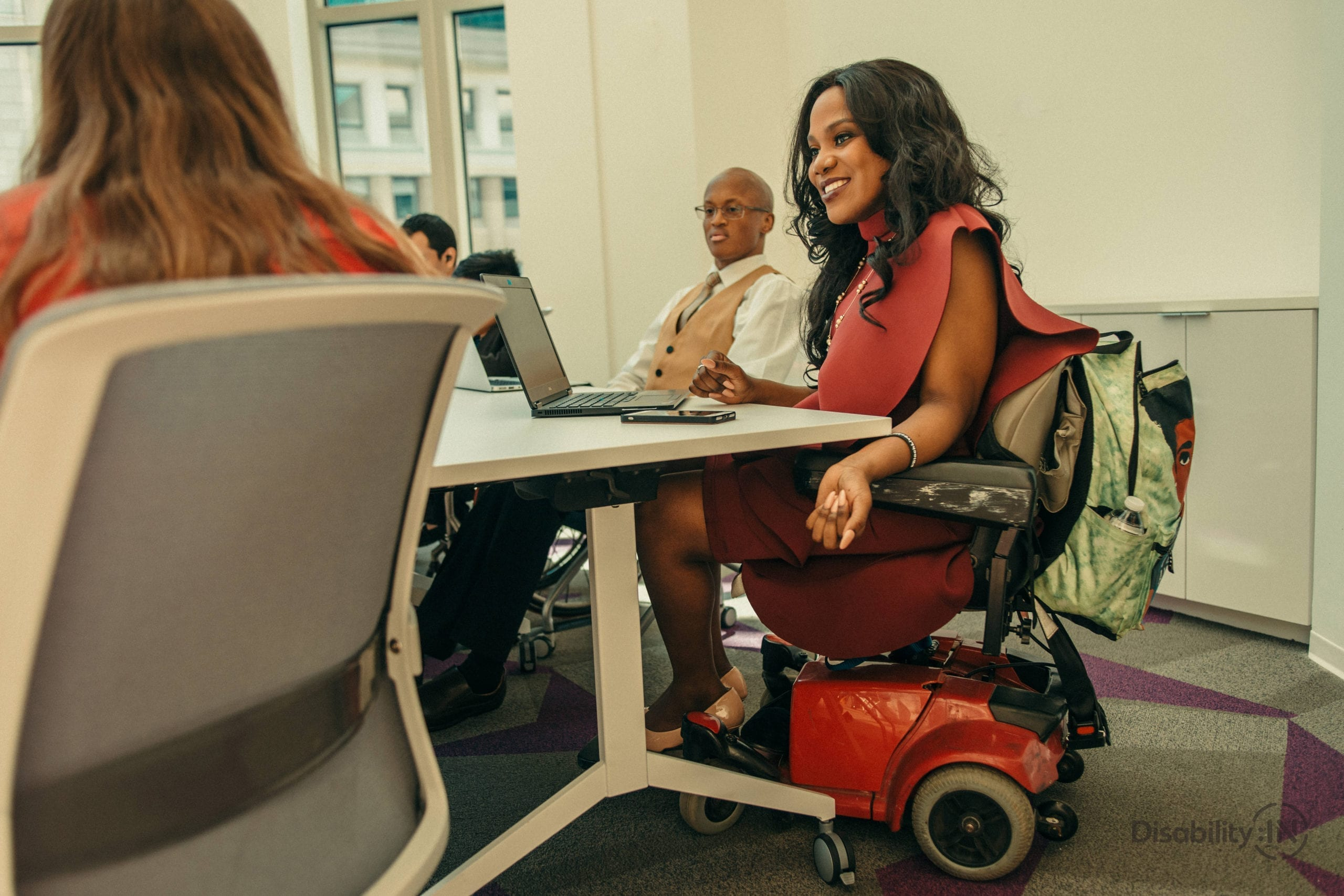 Group of people sit around a board room, focus on women dressed professionally in a motorized wheelchair.