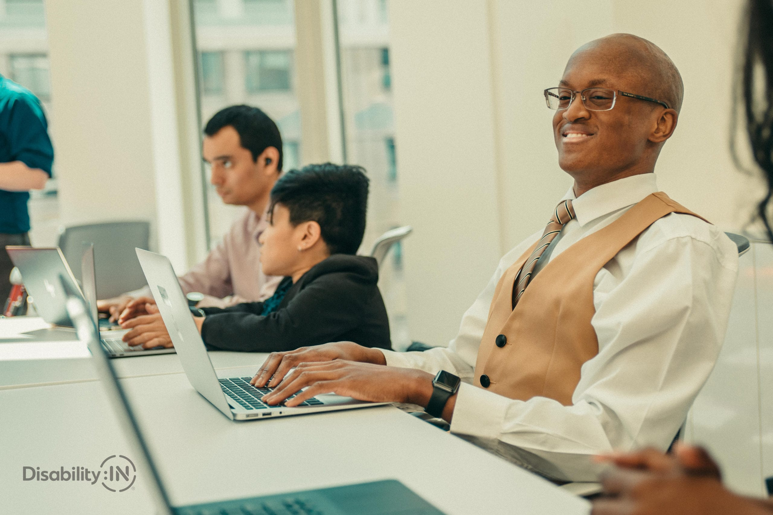 Man sitting at a full conference table on laptop smiling.