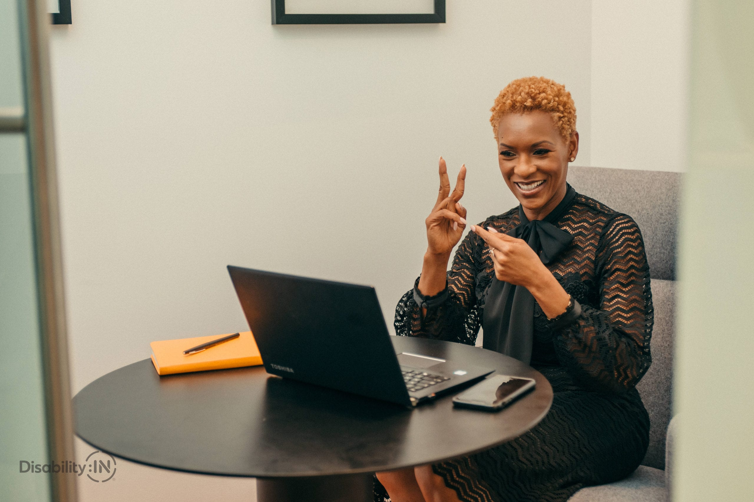 A black woman in a professional setting video conferences while signing into the computer.