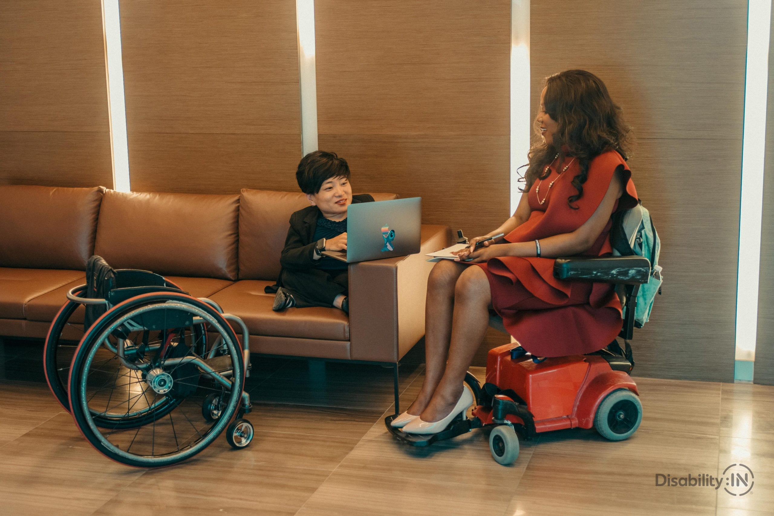 Two women in professional setting discuss work. Both women utilize a wheelchair.