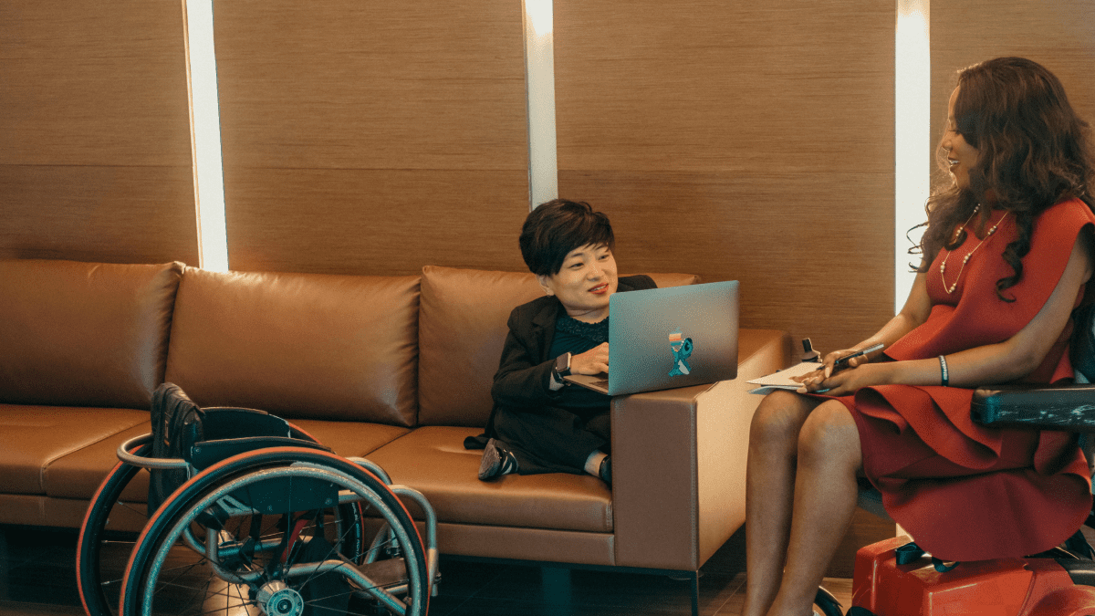 A person of short stature sitting on a couch, using a laptop, with their wheelchair next to the couch. They are wearing a black suit and have cropped black hair. They are speaking to a woman with long black hair in a flowing red dress.