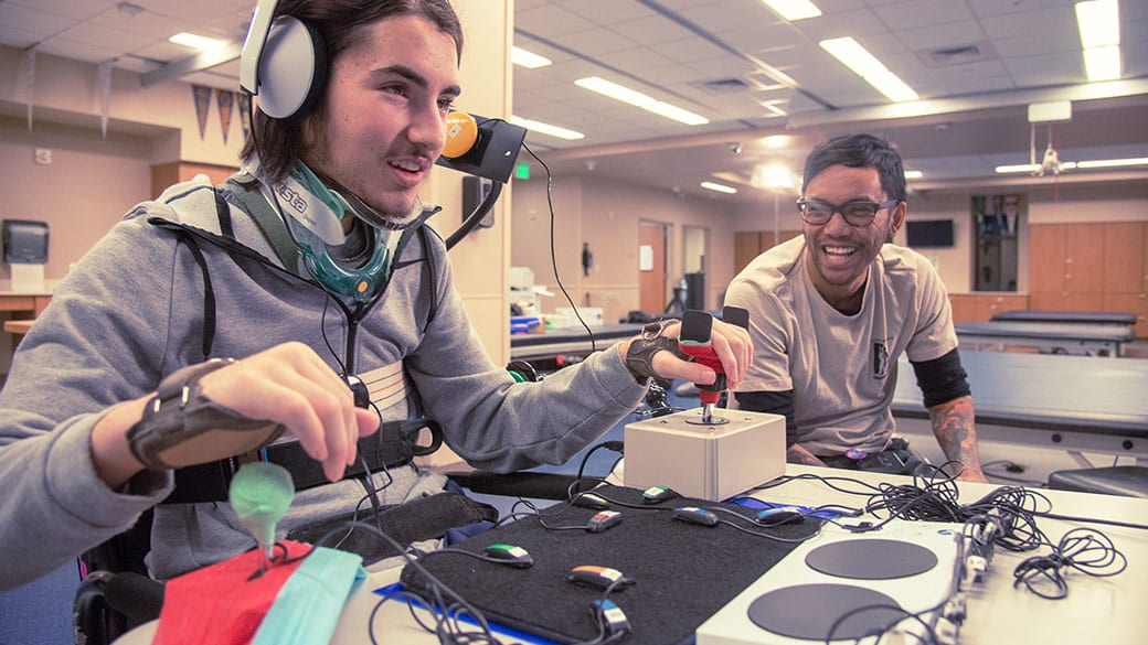 A person testing out Microsoft's new Xbox Adaptive Controller with another person nearby. The person using the controller is wearing a head set and has fair skin and is wearing a headset. The other person has black hair and is wearing glasses and is watching them with a smile.